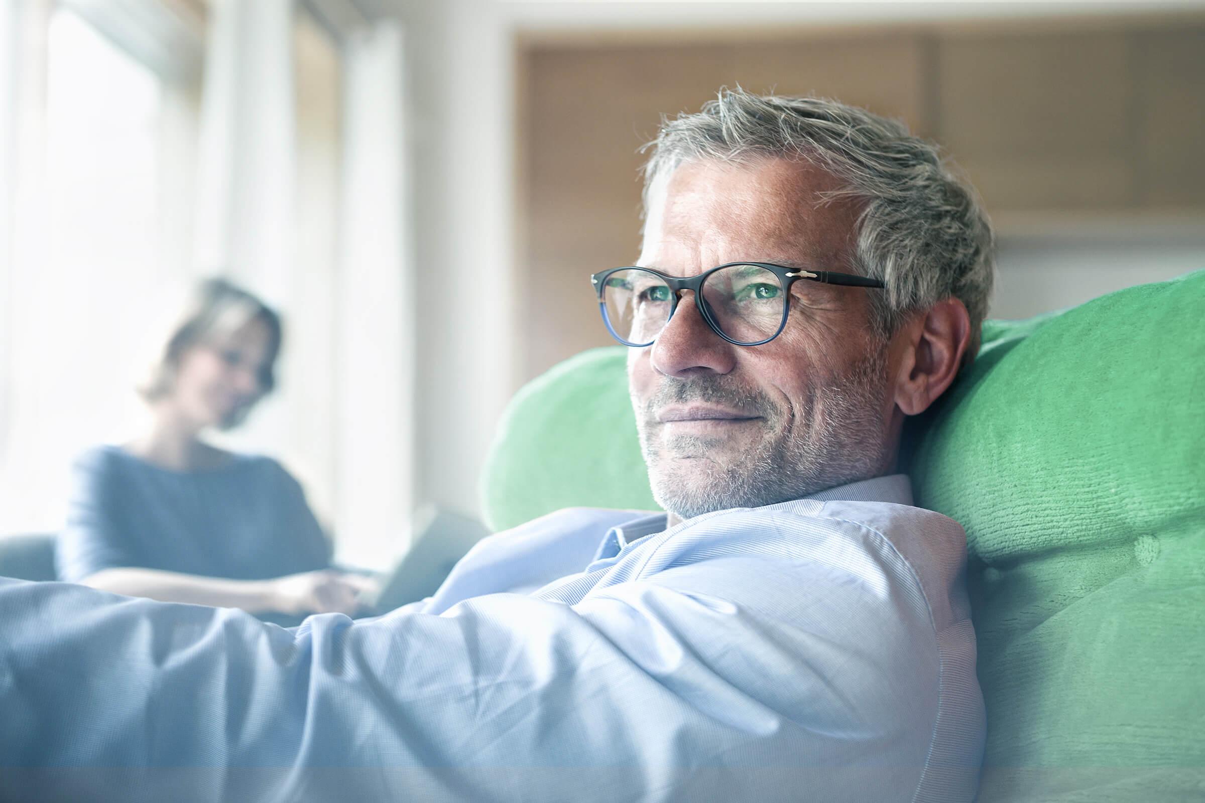 Zadowolony inwestor ETF i akcji siedzący na kanapie