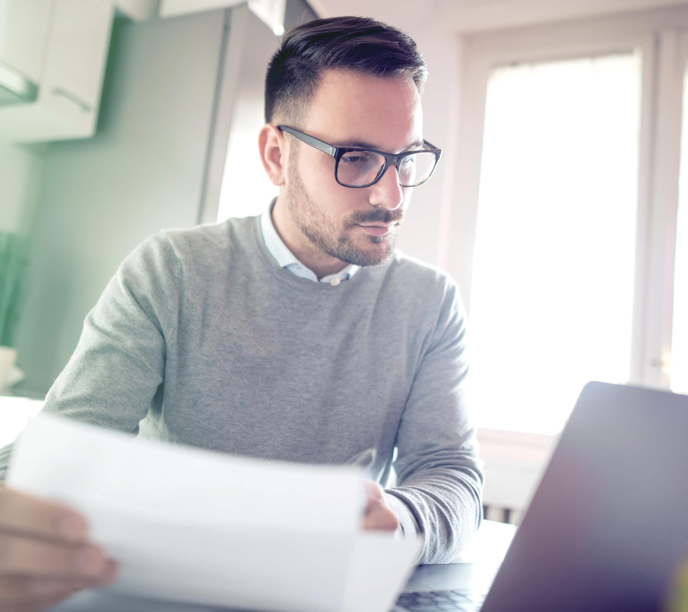 Inwestor patrzący na laptop zainteresowany niskimi opłatami u brokera internetowego LYNX