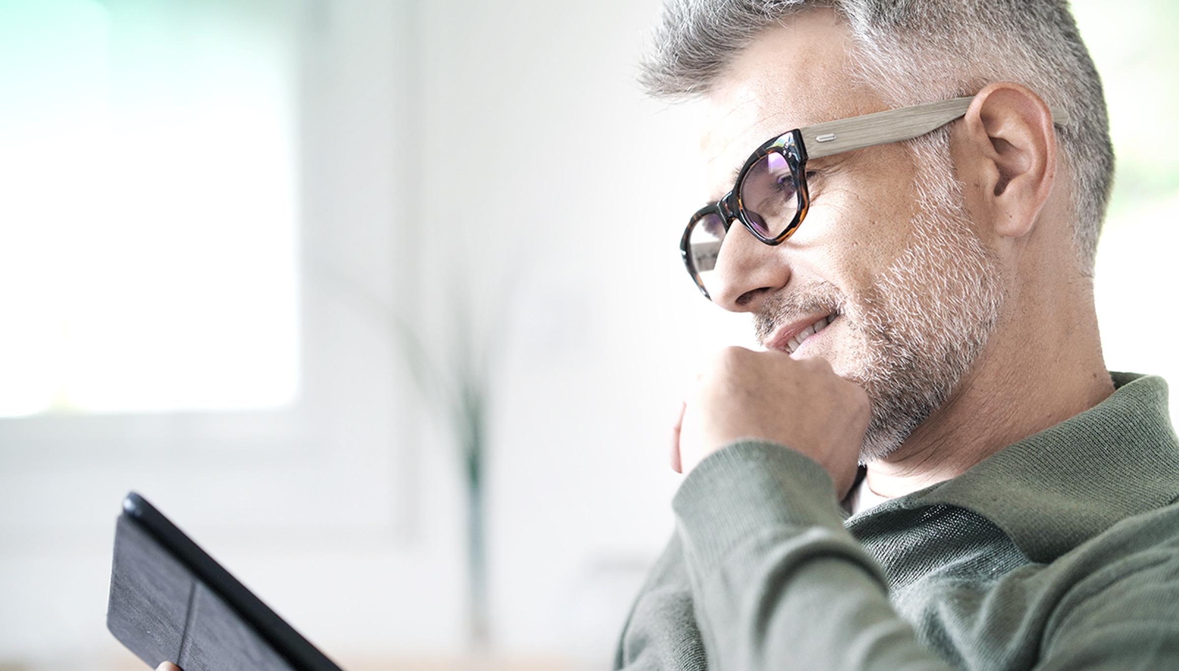 Zadowolony inwestor i klient LYNX sprawdzający swój portfel inwestycyjny na tablecie