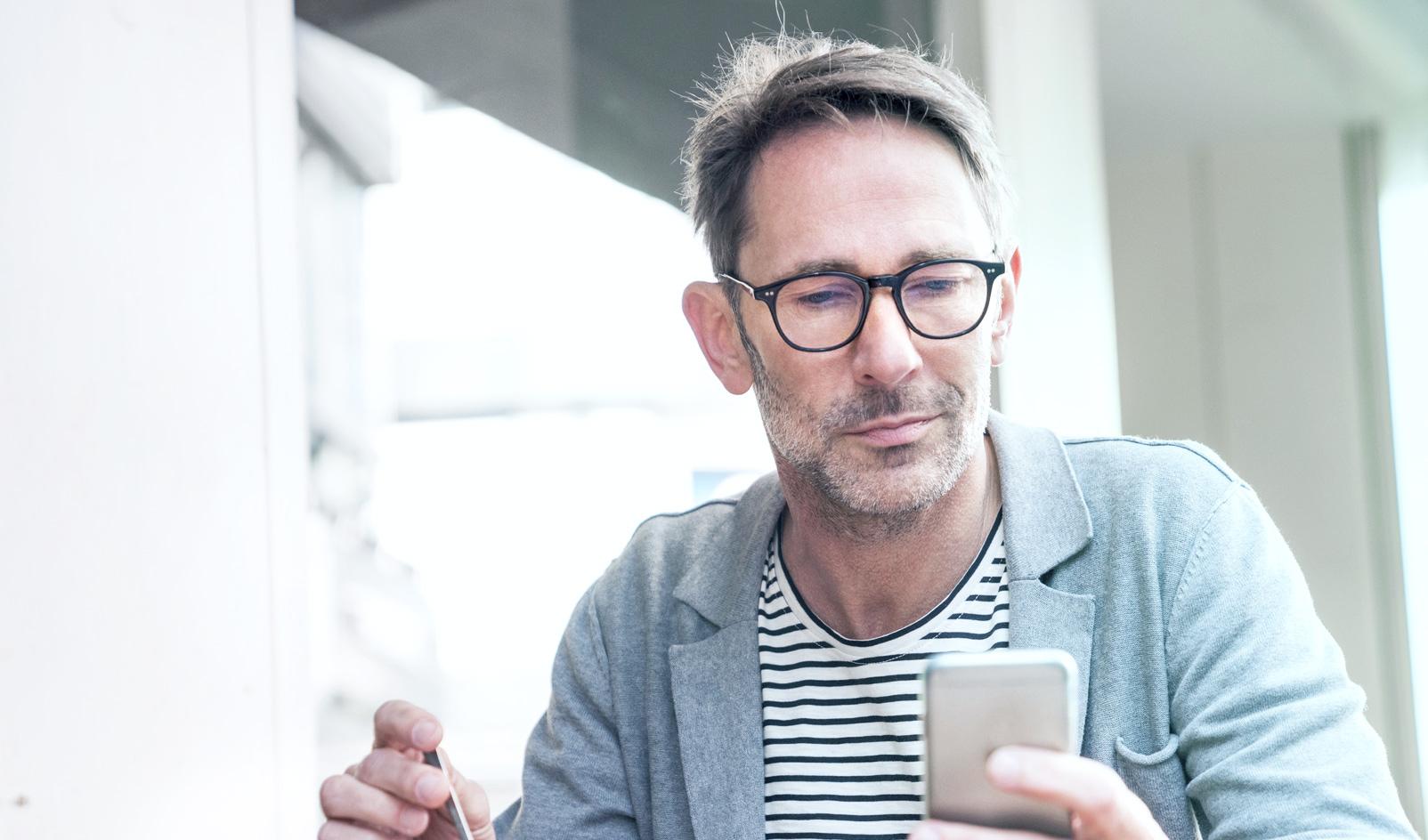 Zadowolony inwestor i klient LYNX, który handluje na giełdzie za pomocą smartfona