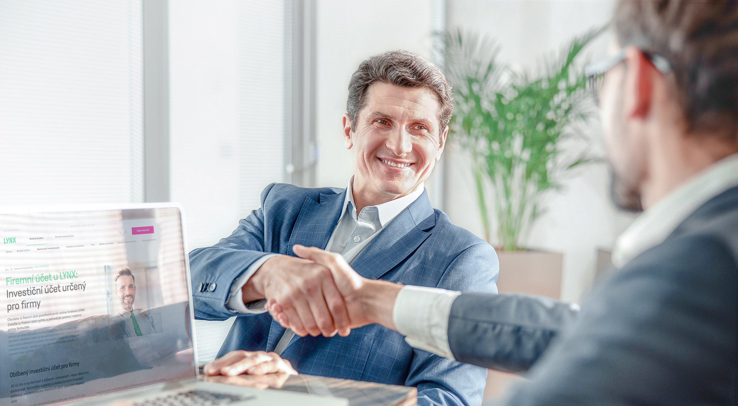 Zadowolony inwestor ściskający dłoń pracownikowi LYNX po otwarciu konta firmowego
