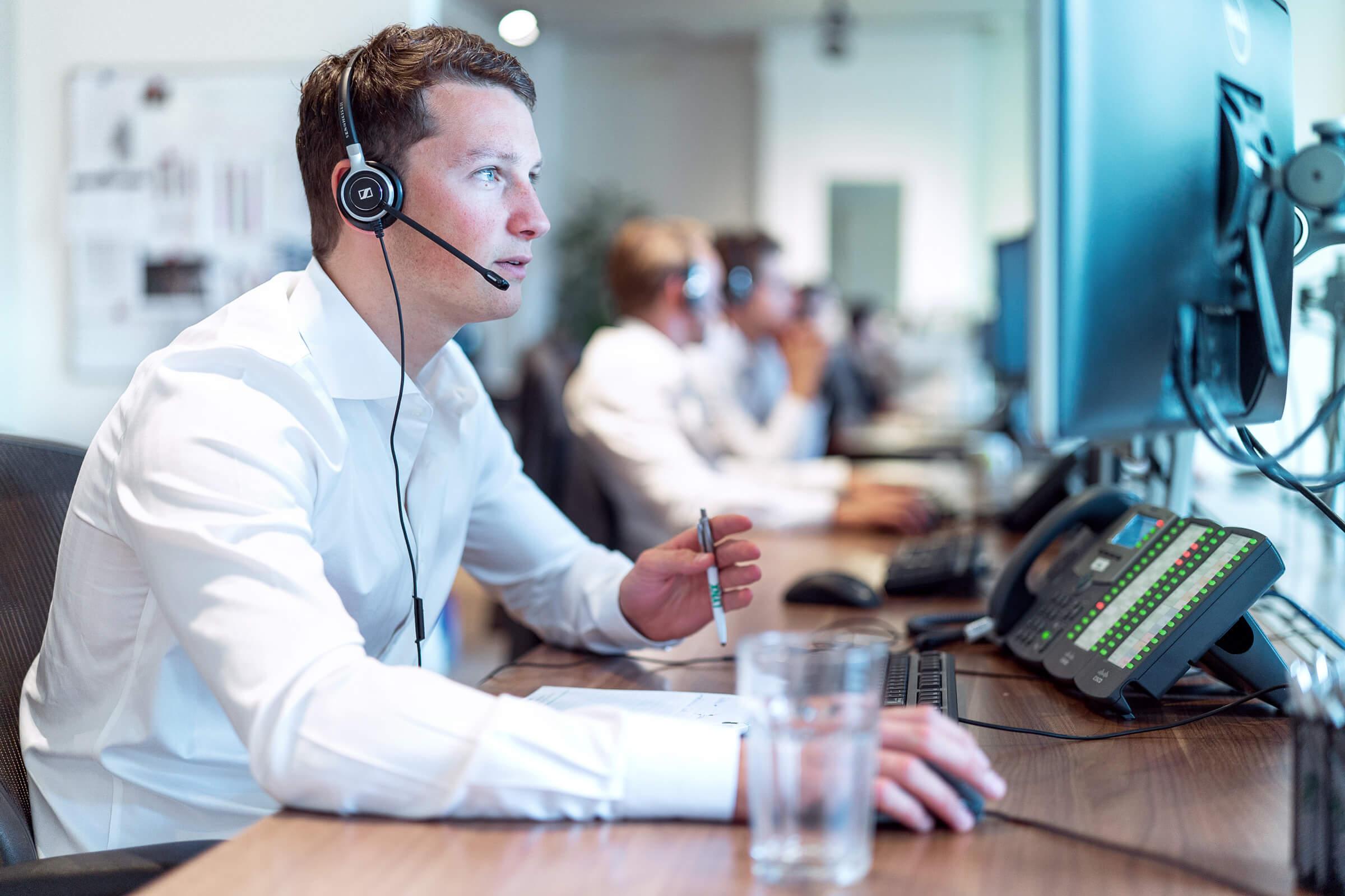 Przeszkolony pracownik brokera internetowego LYNX doradza klientowi w ustawieniu platformy transakcyjnej